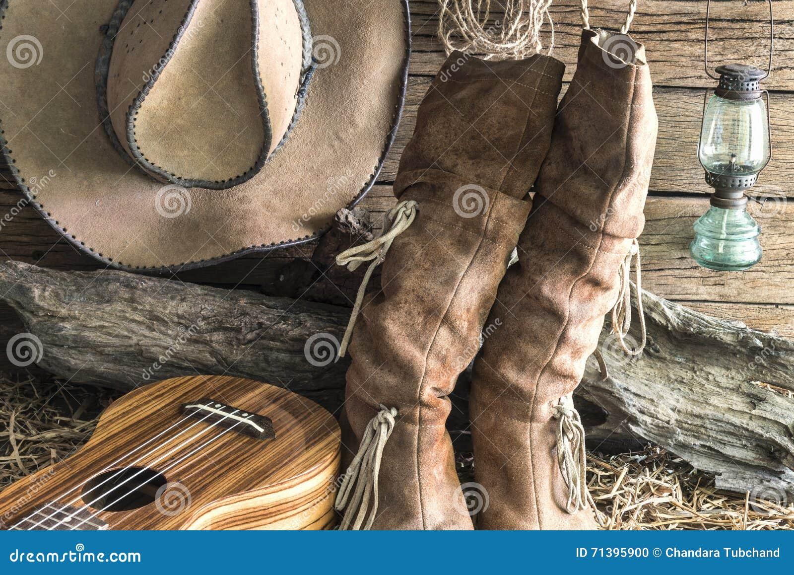 El marrón del oeste americano del rodeo del primer sentía el sombrero de  vaquero y las botas de cuero tradicionales con el ukelele en el fondo del  granero ... 98534516244