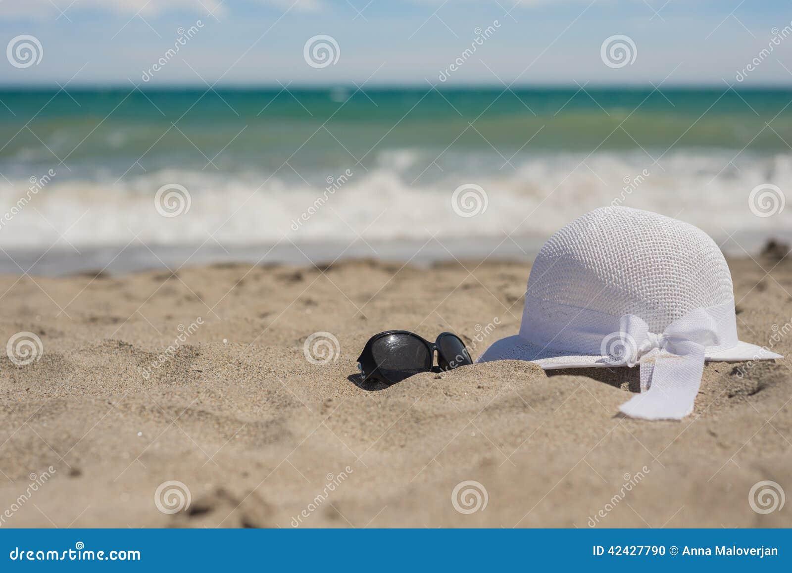 Sombrero y gafas de sol de mimbre en la playa