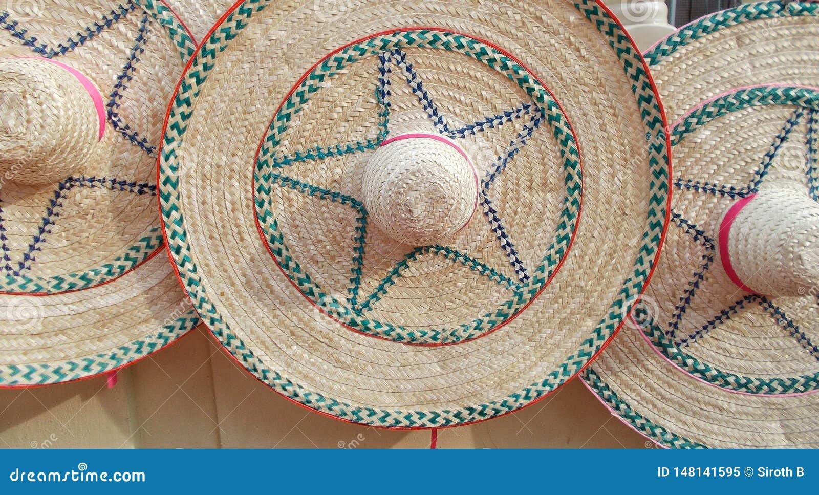Sombreros de paja grandes de las mujeres elegantes y coloridos en el paseo de la calle de mercado durante verano el días soleados
