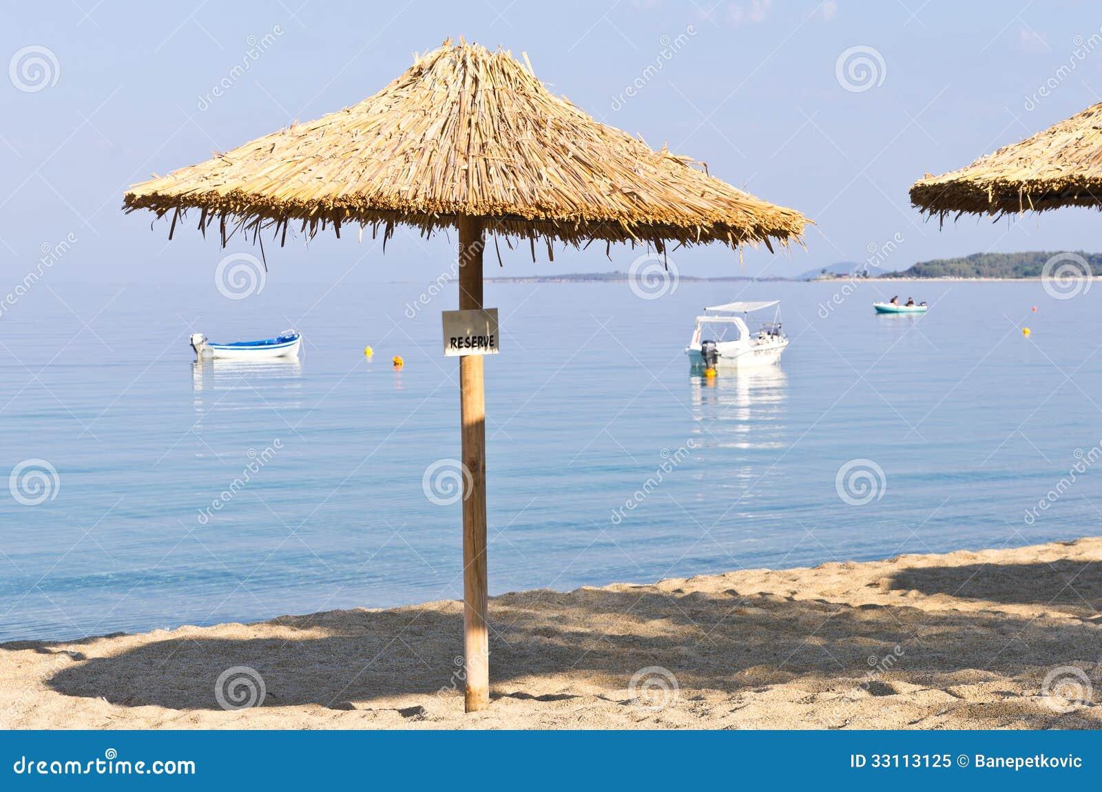 Sombrilla cubierta con paja en una playa reservada para - Sombrillas para piscinas ...