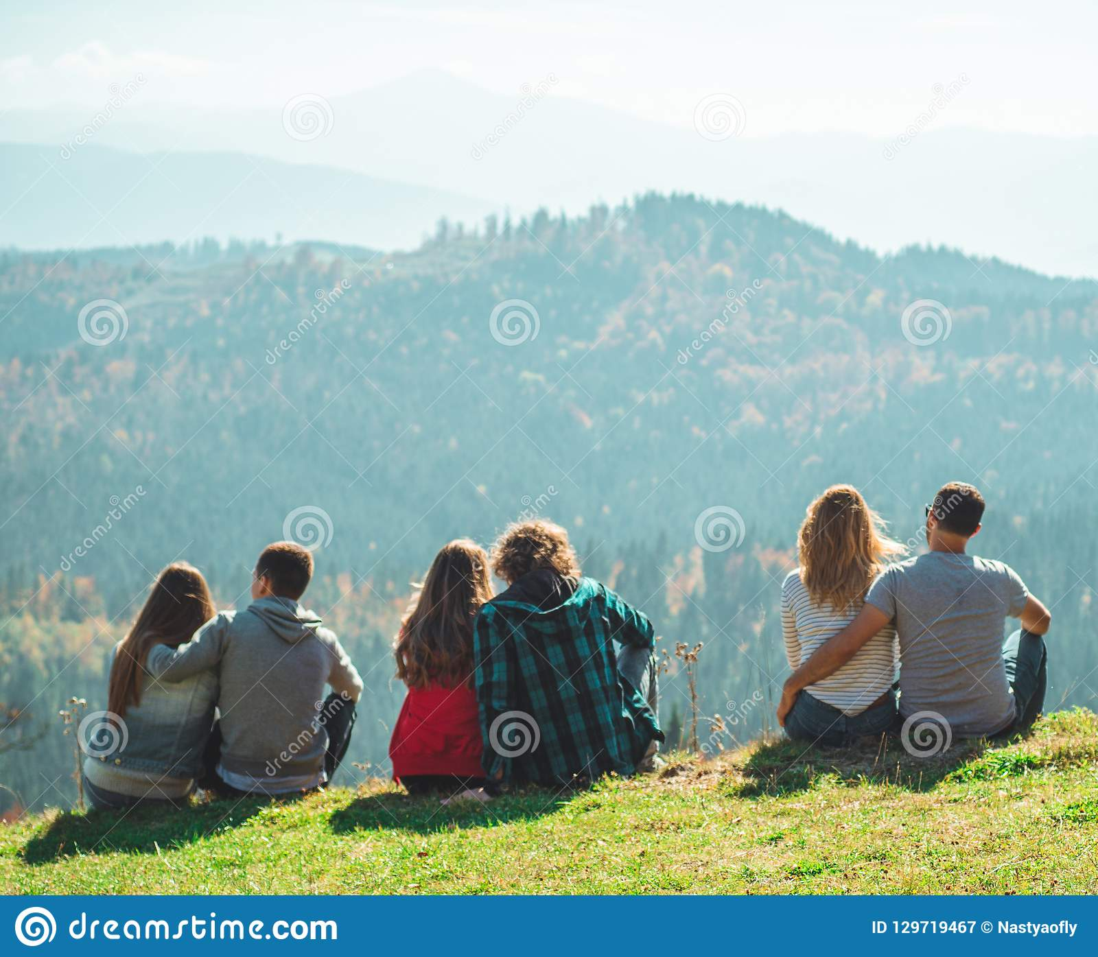 Some Couple travelers Boys and Girls sitting on cliff happy emotions Lifestyle concept Young family traveling active