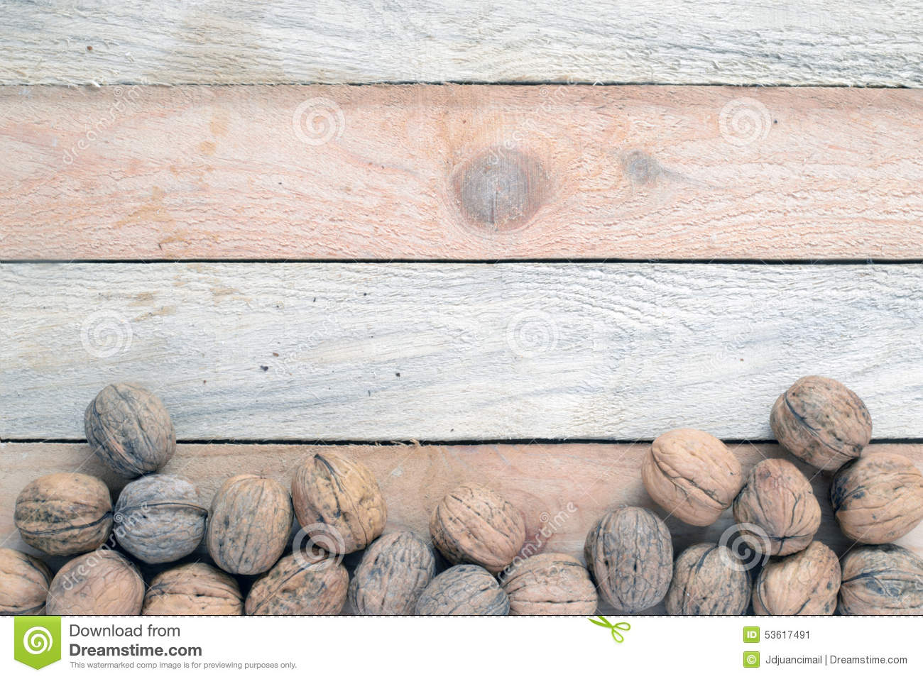 Some nuts scattered on a WOODEN TABLE.