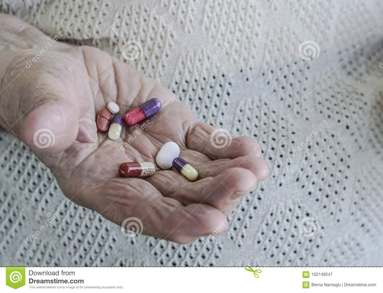Pills on palm of a senior woman
