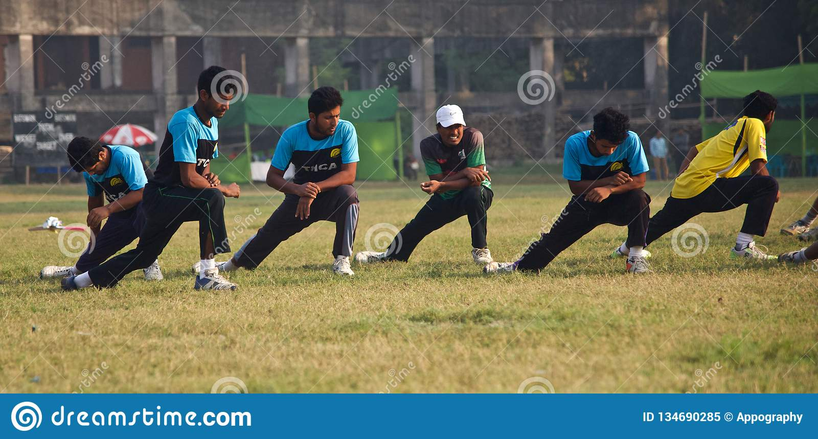 Young players stretching around a cricket ground