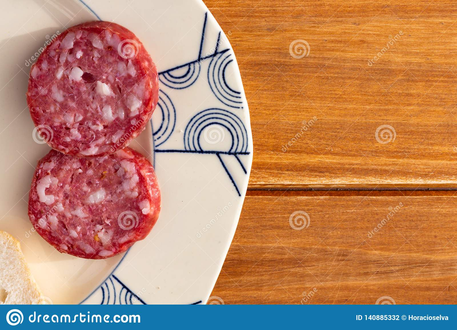 Some slices of salami on an old ceramic plate on a wooden rustic table. Food for a snack