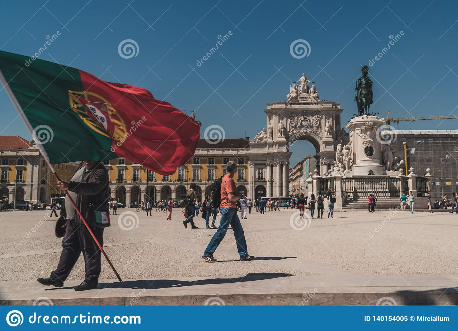 Someone holds a giant flag of Portugal on the Praça do Comércio Commerce Square in downtown Lisbon.