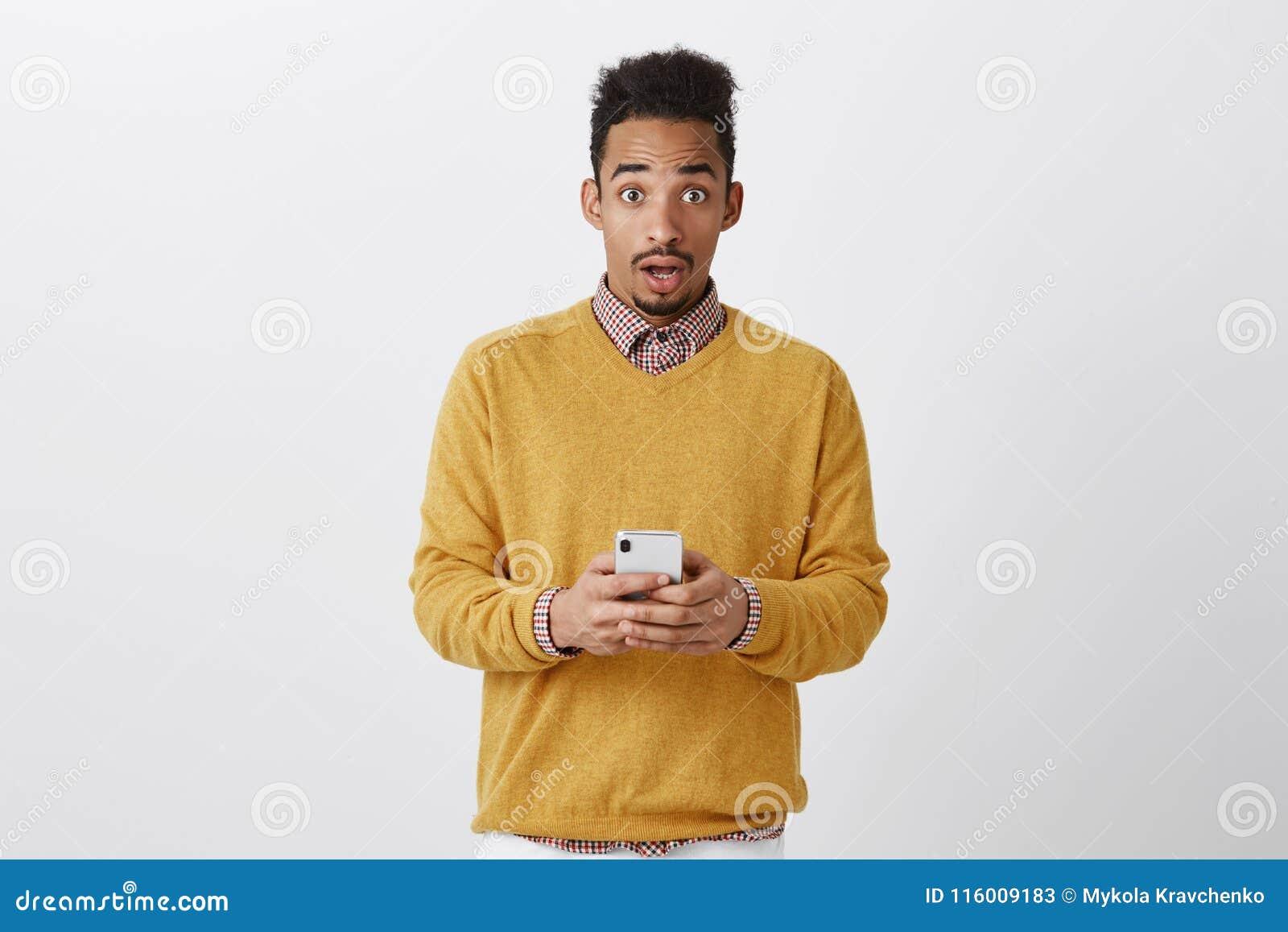 Someone próbujący siekać jego telefon Szokujący przystojny chłopak z afro fryzurą w modnym odzieżowym mienia smartphone