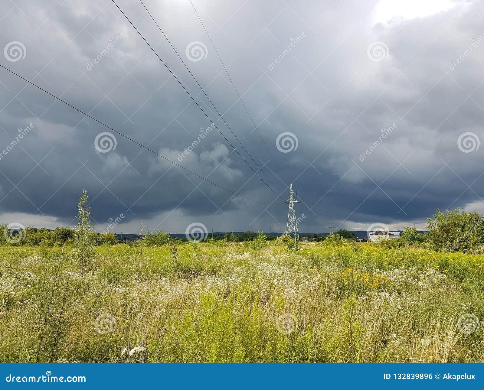 Sommaräng i strålarna av solen med en överhängande åskmoln- och elektricitetslinje Väderändring Storm på en solig dag