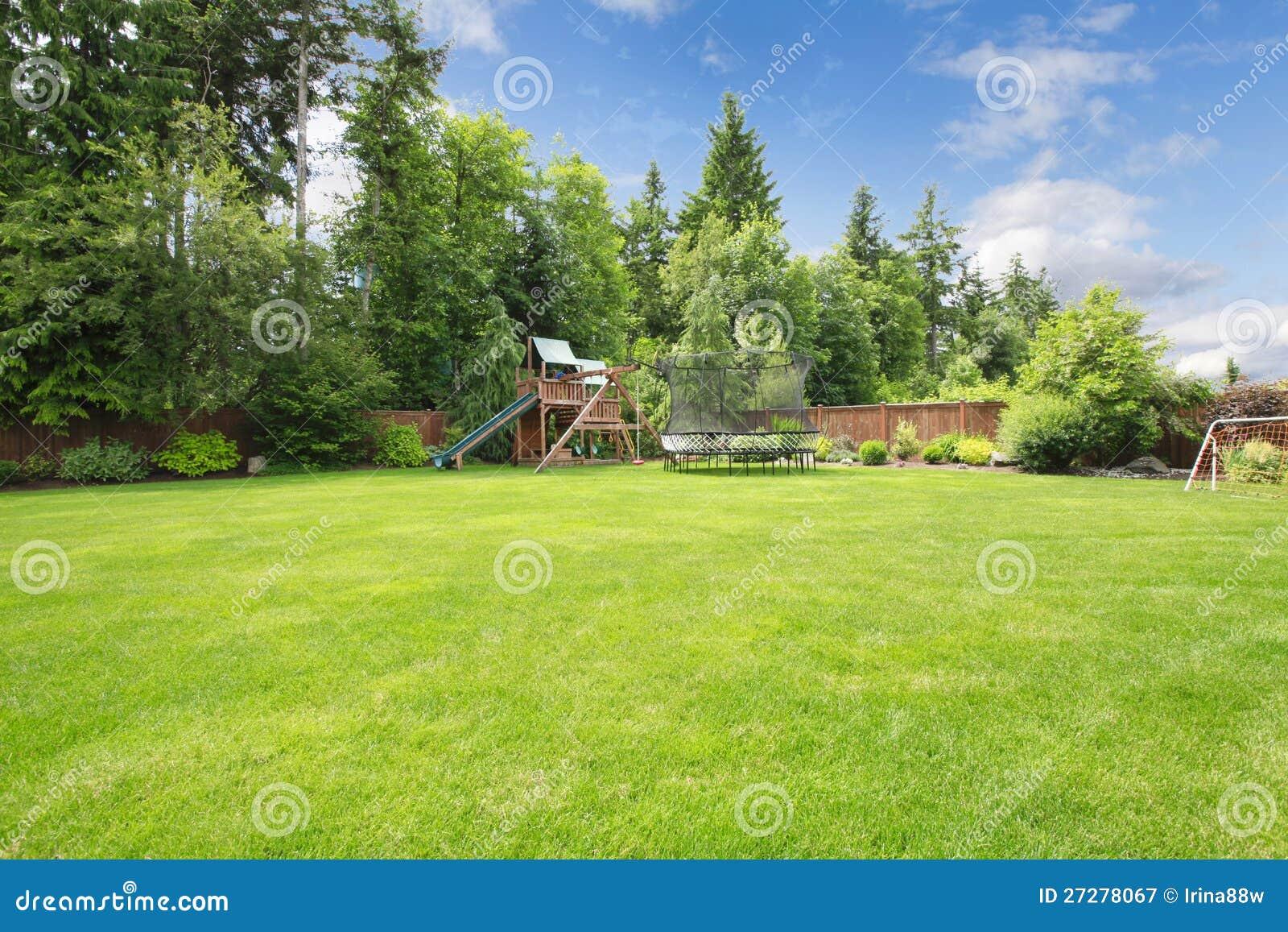 Sommar fäktad trädgård med spelrumområde.