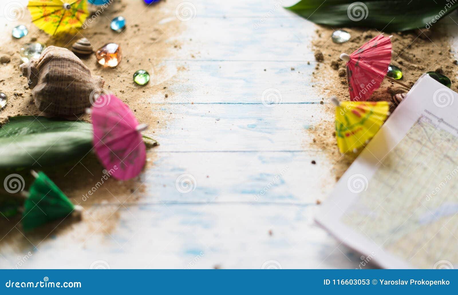 Sommar för snäckskal för sand för bakgrundsbegreppsram Paraplyer för coctailar på sand på en träbakgrund med kiselstenar