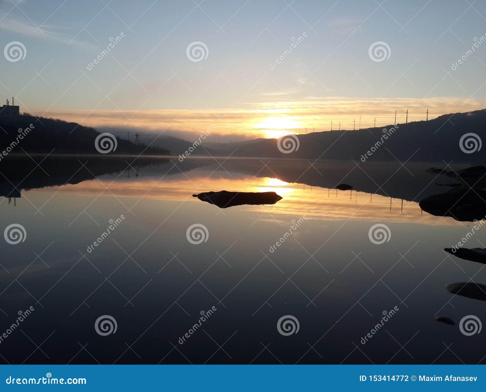 Sommar i den arktiska cirkeln Starten av den mörka tidspunkten, med en underbar utgående sol, på bakgrunden av sjön och Het