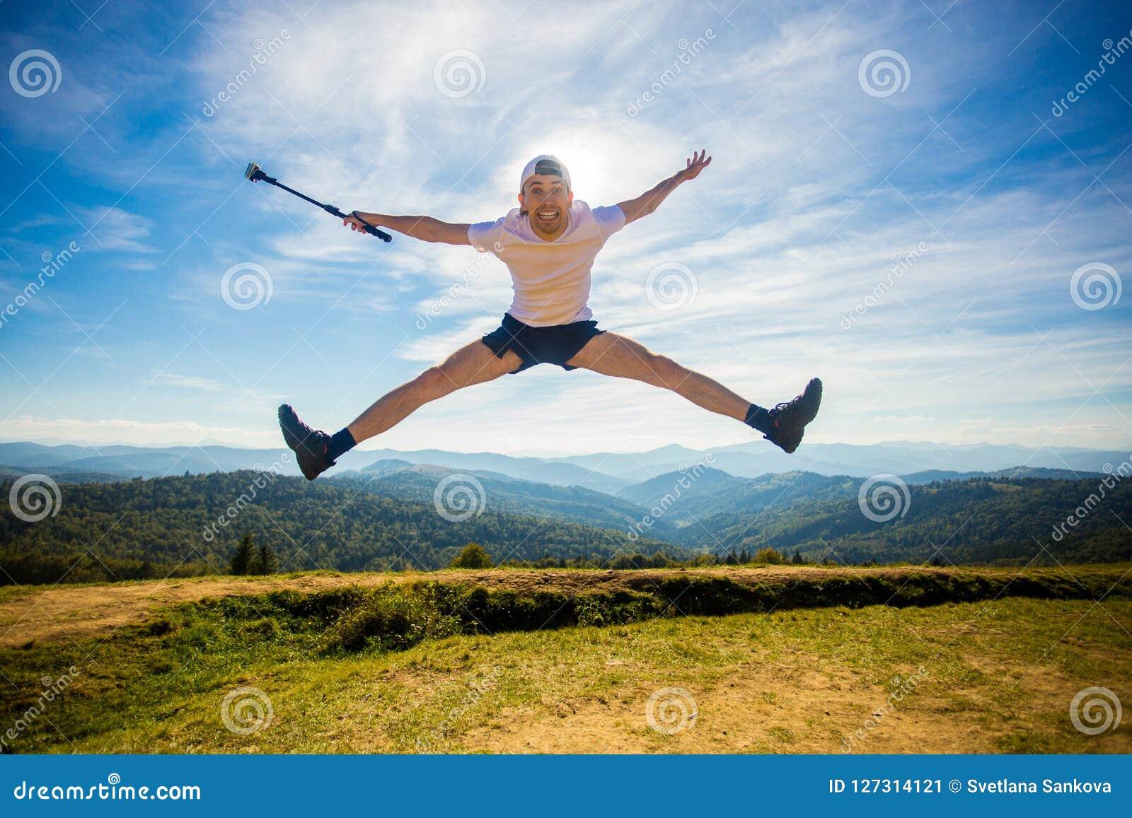 Sommar som fotvandrar i berg Den unga turist- mannen i lock med händer upp av berg beundrar överst naturen