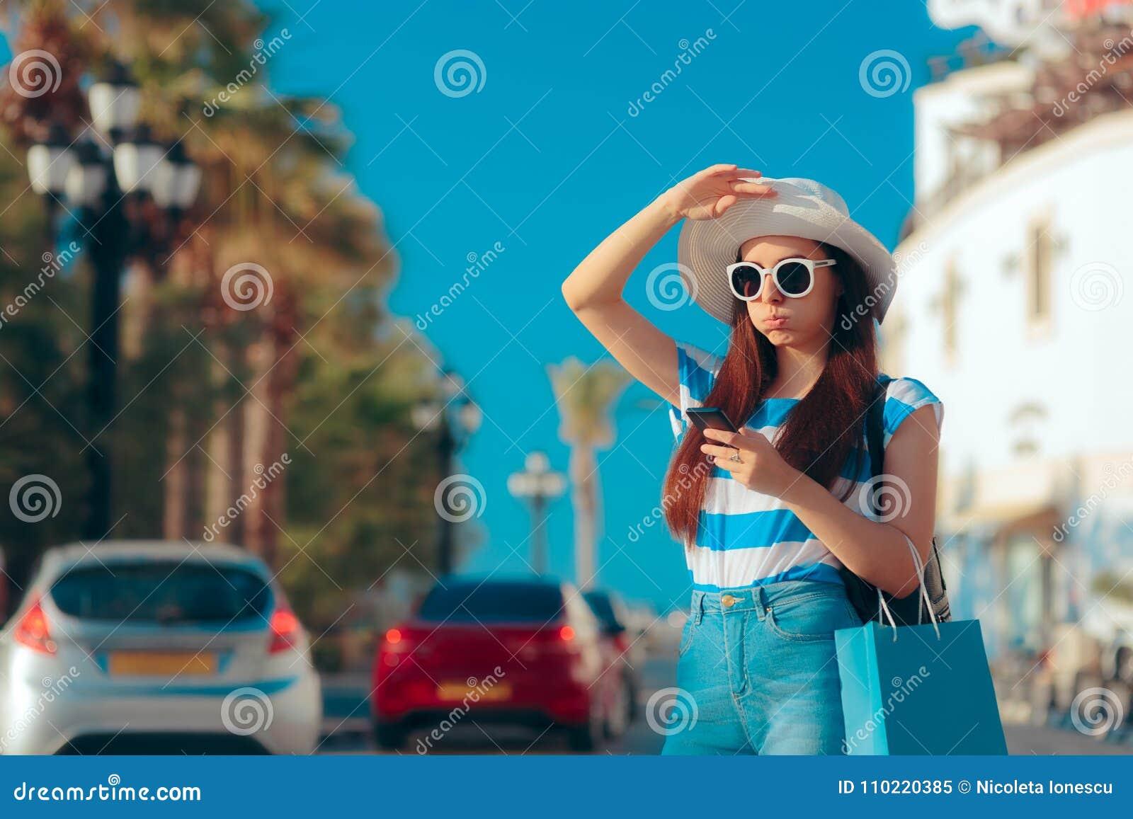 Sommarflicka med shoppingpåsen och Smartphone som söker efter taxien