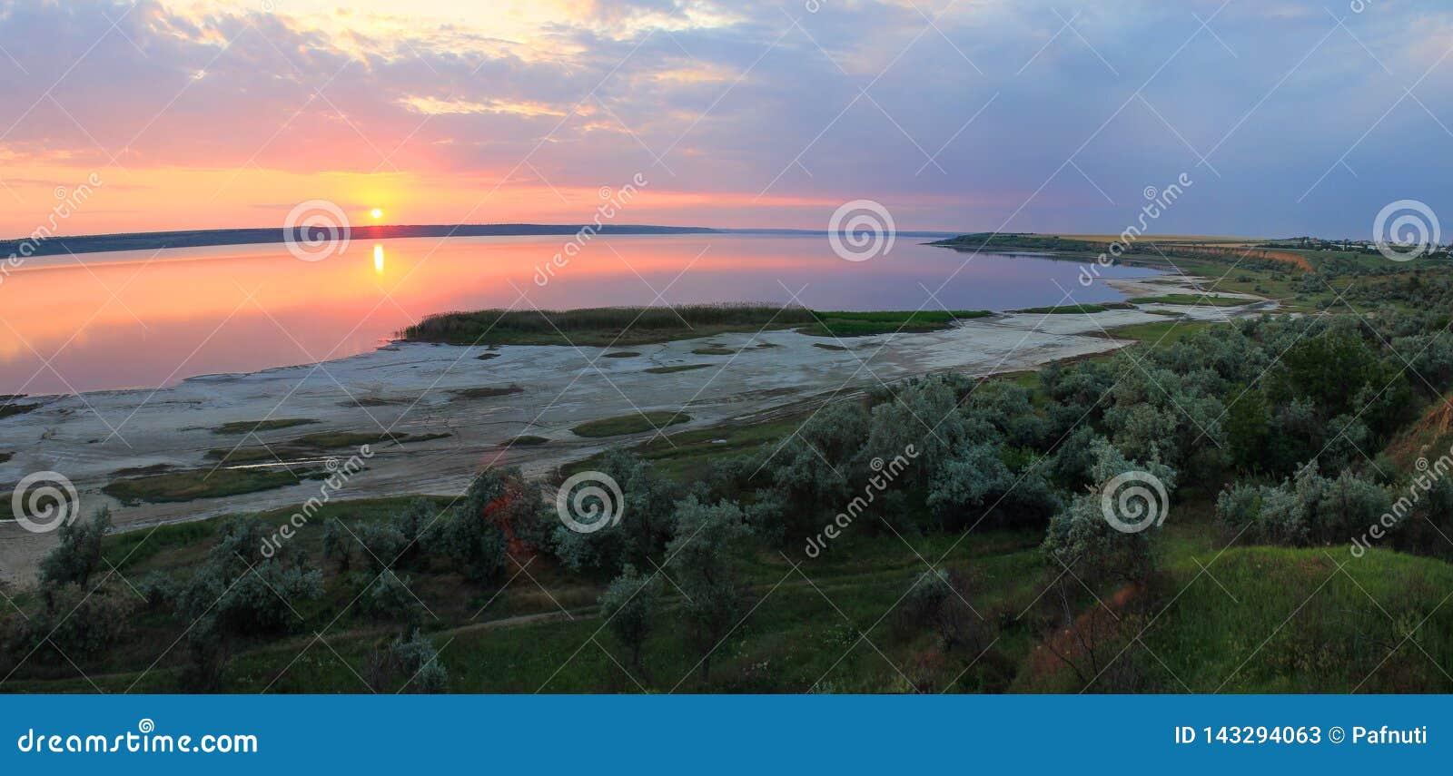 Sommarlandskap på bankerna av sjön på solnedgången