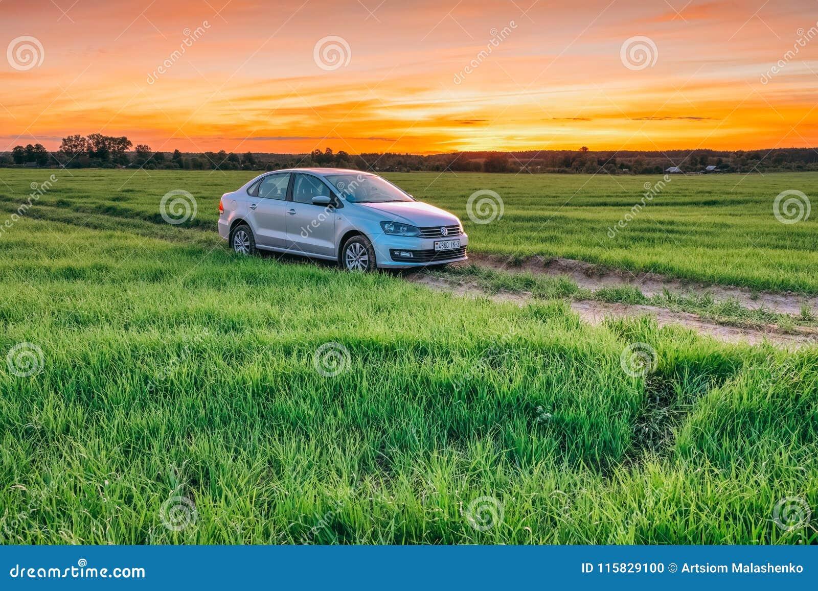 Sommarlandskap på solnedgången med den Volkswagen Polo Vento maskinen in