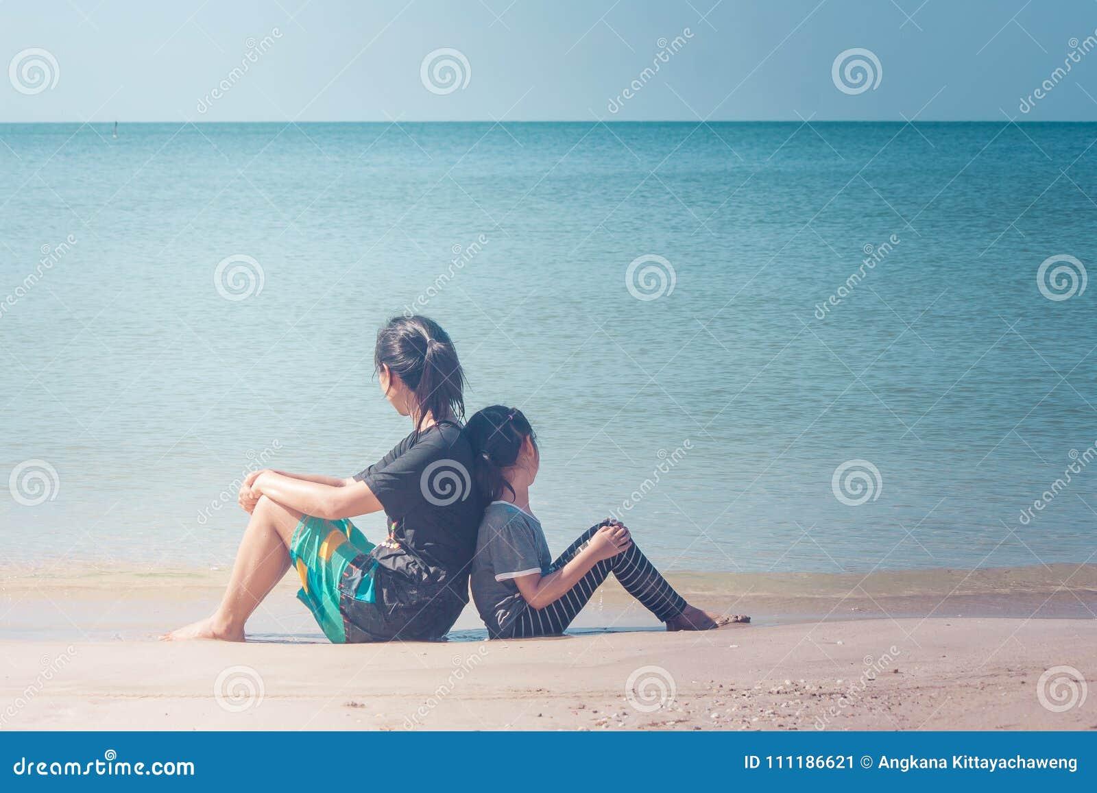 Sommarsemester och feriebegrepp: Den lyckliga familjdagsutflykten på havet, kvinnan och barnet som tillbaka sitter för att dra ti