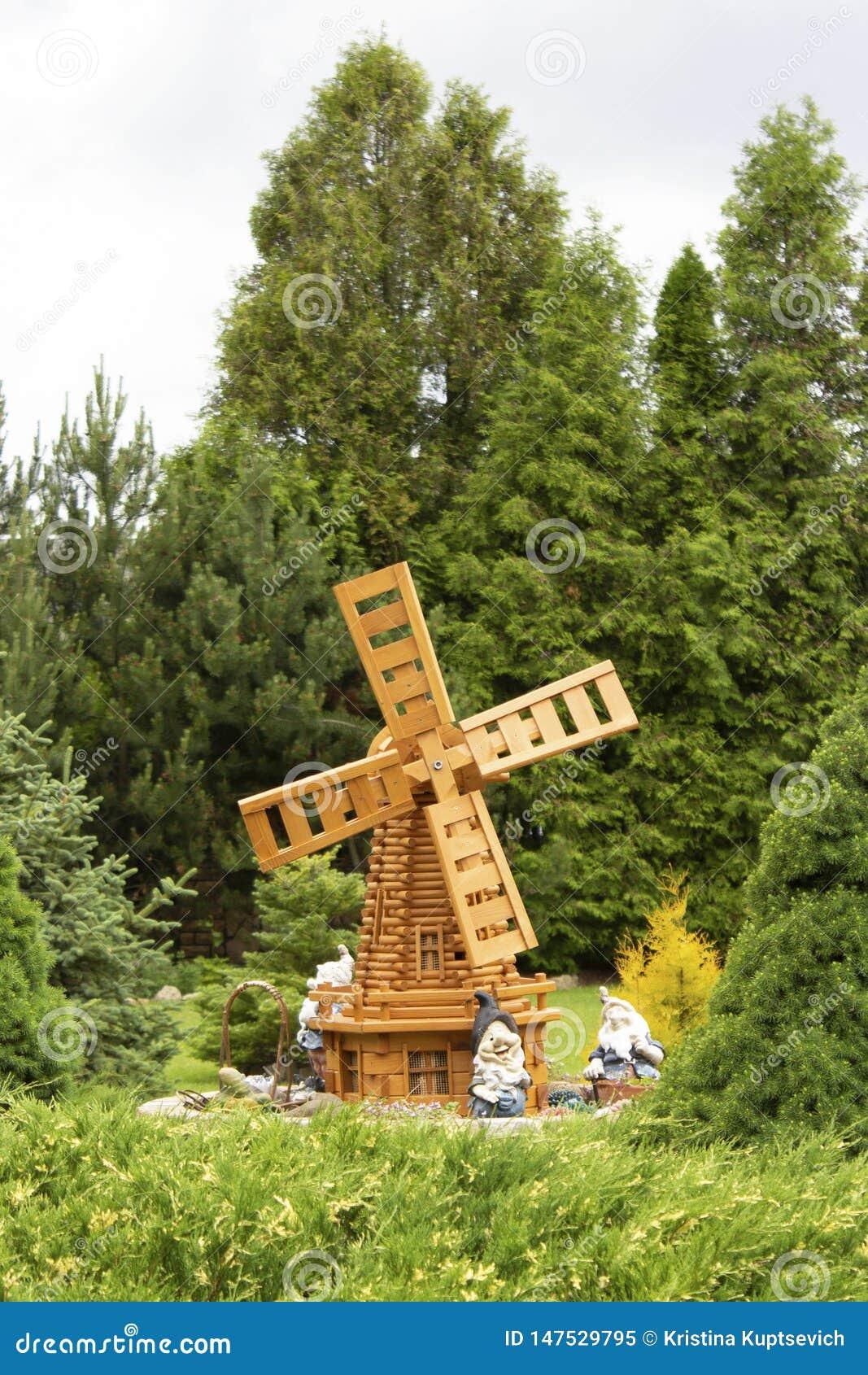 Sommarträdgård med en dekorativ väderkvarn och gnomer