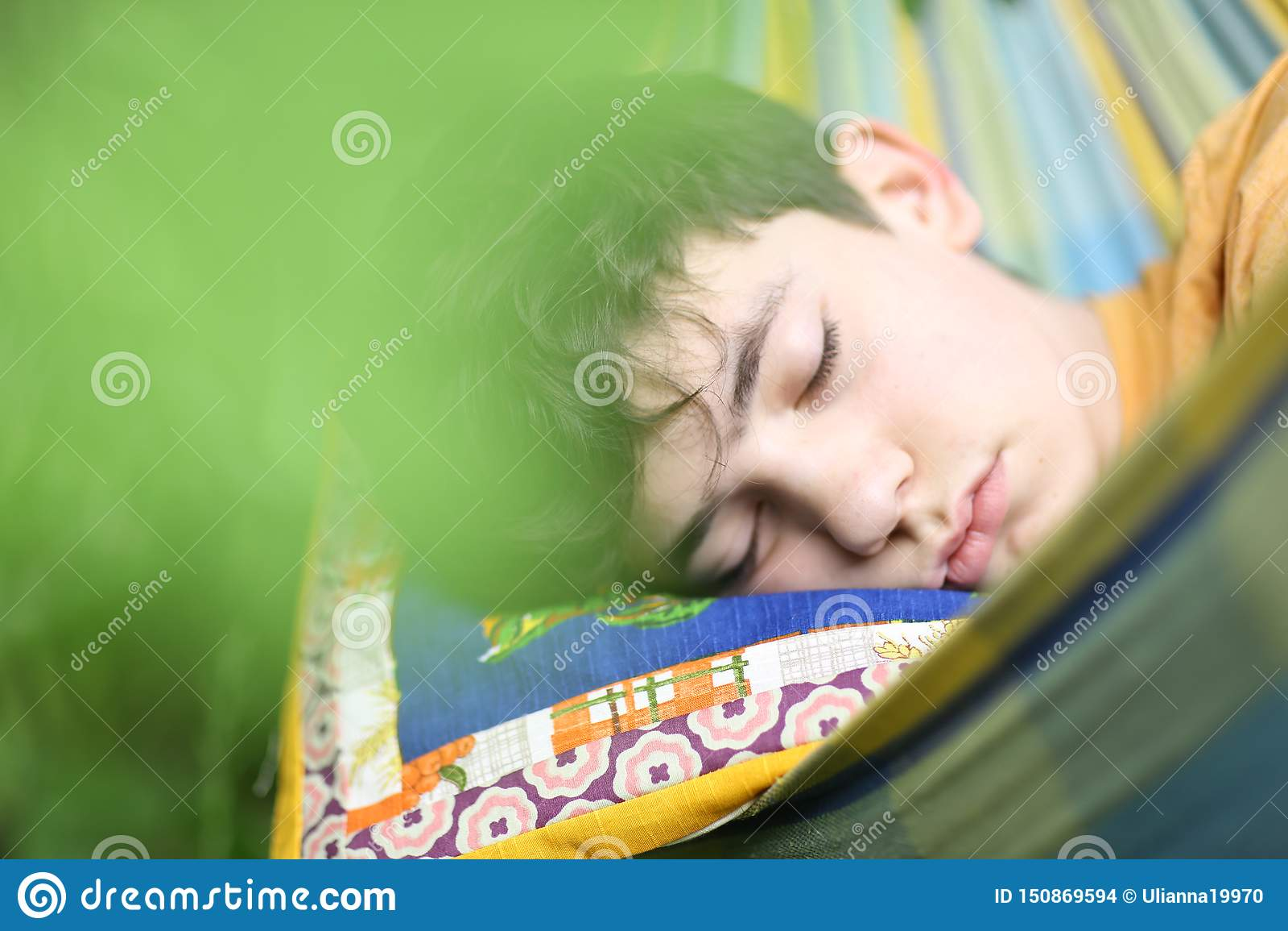 Sommeil de repos de garçon d adolescent avec le livre dans l hamac sur le jardin vert d été