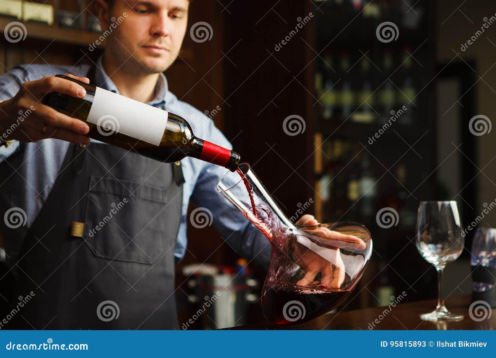 Sommelier dolewania wino w szkło od dekantatoru męski kelner