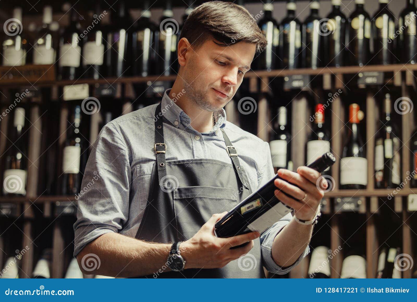 Sommelier joven que sostiene la botella de vino rojo en sótano