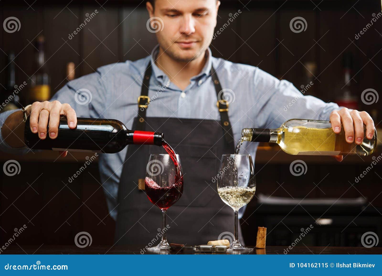 Sommelier masculino que vierte el vino blanco rojo y en las copas de tallo largo