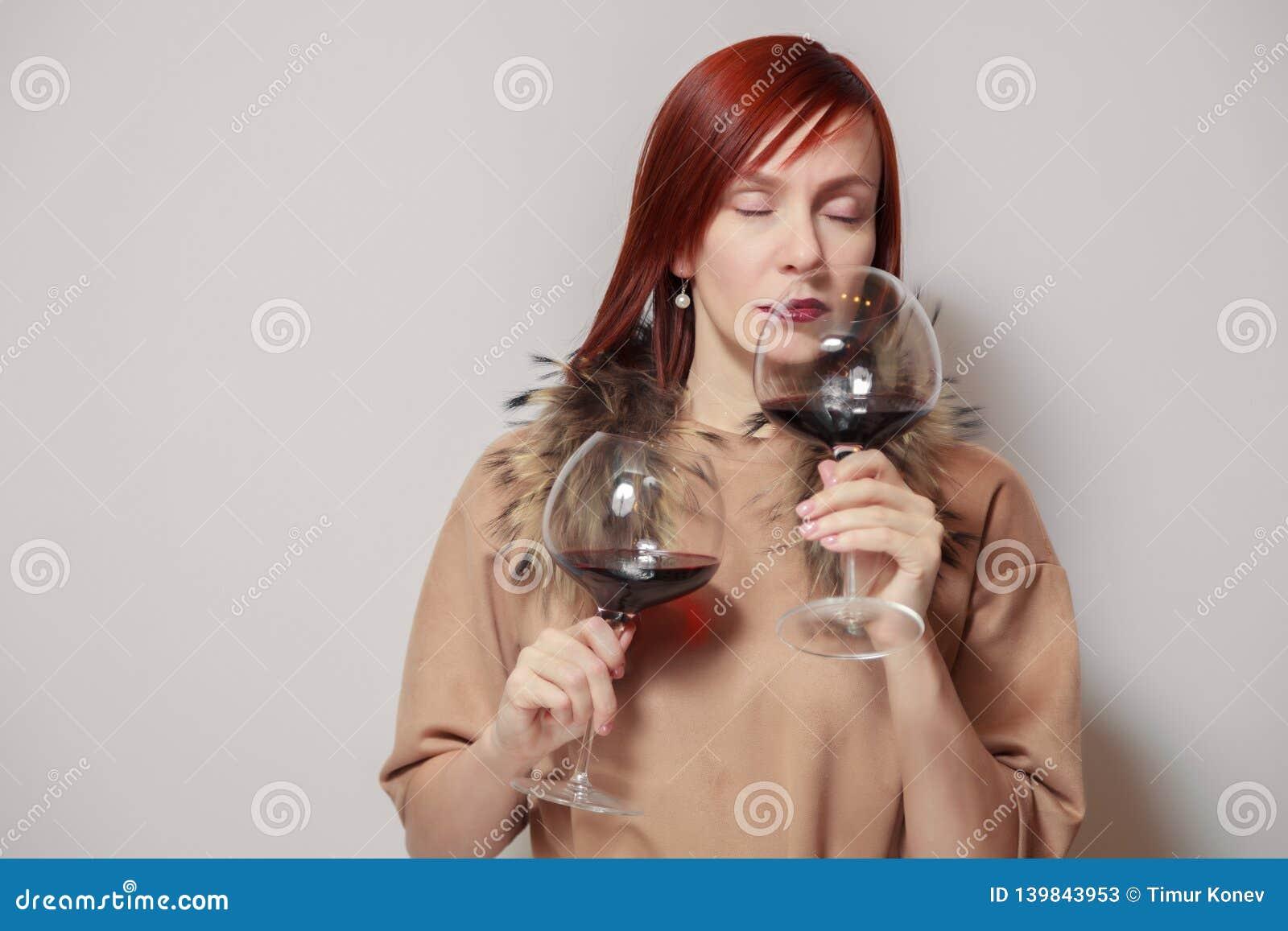 Sommelier pelirrojo divertido joven de la muchacha con el cabo de la piel en el control y el olor blancos del fondo dos vidrios d