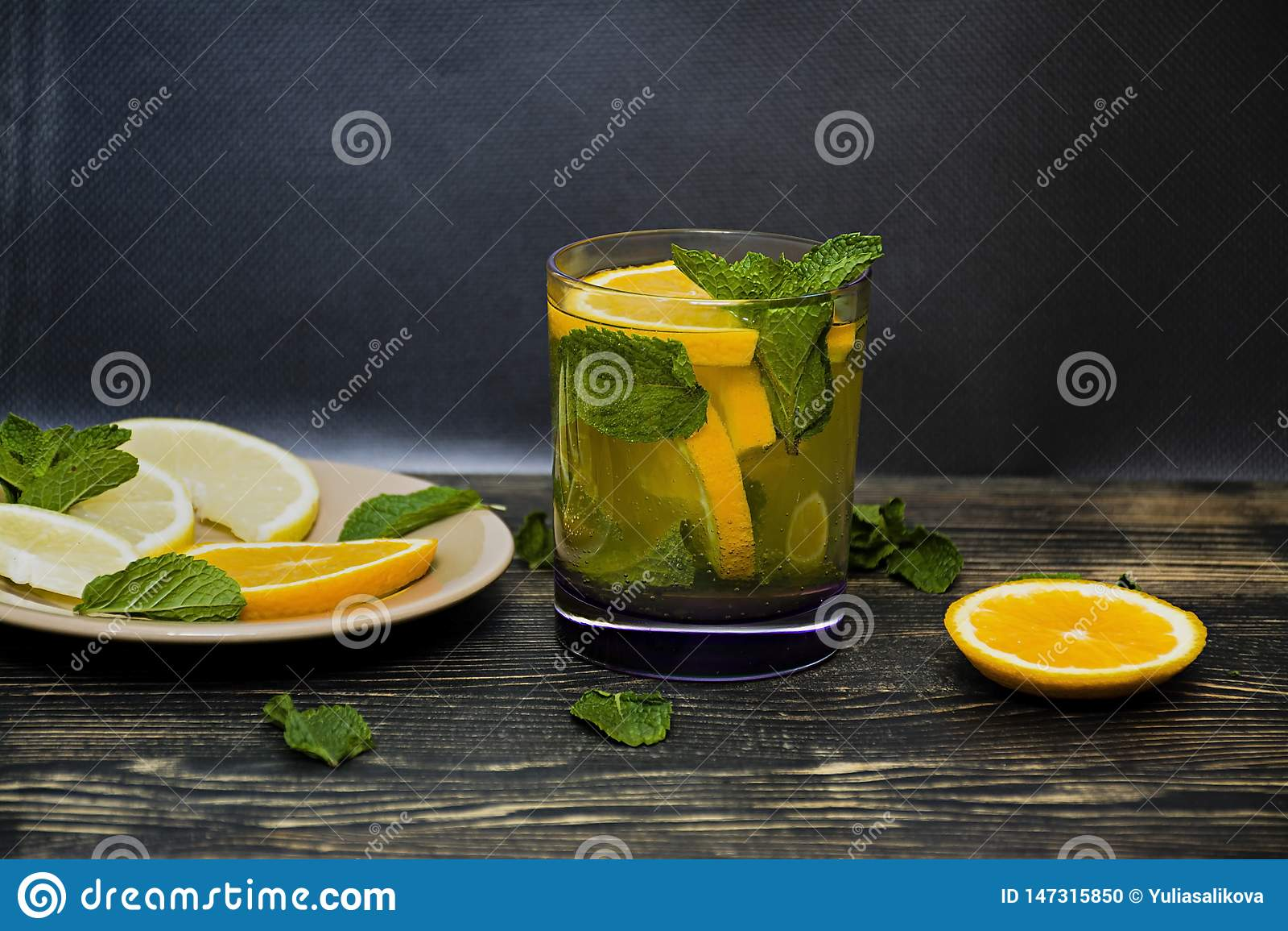 Sommer, erneuerndes Orangensaftgetr?nk mit den tadellosen und orange Scheiben Dunkler h?lzerner Hintergrund Weicher Fokus