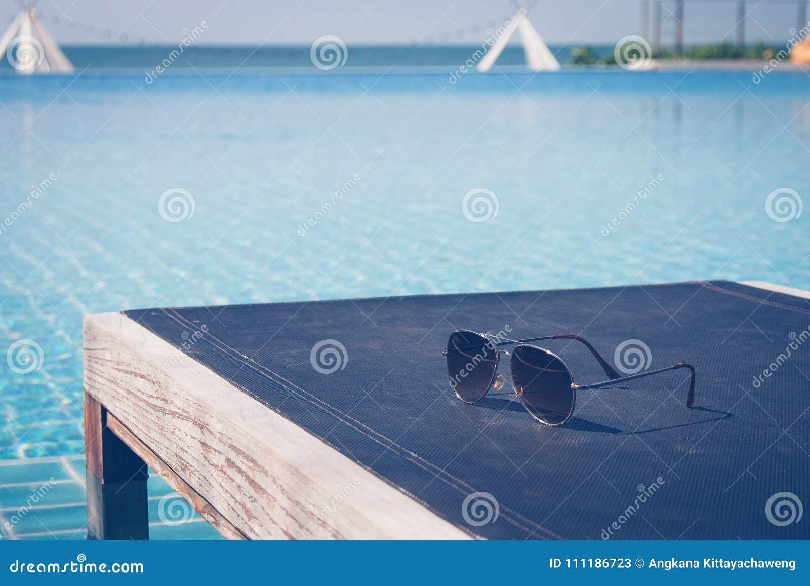 Sommer-Ferien und Feiertags-Konzept: Sonnenbrille setzte an hölzernen Daybed in Swimmingpool mit Meerblickansicht in Hintergrund