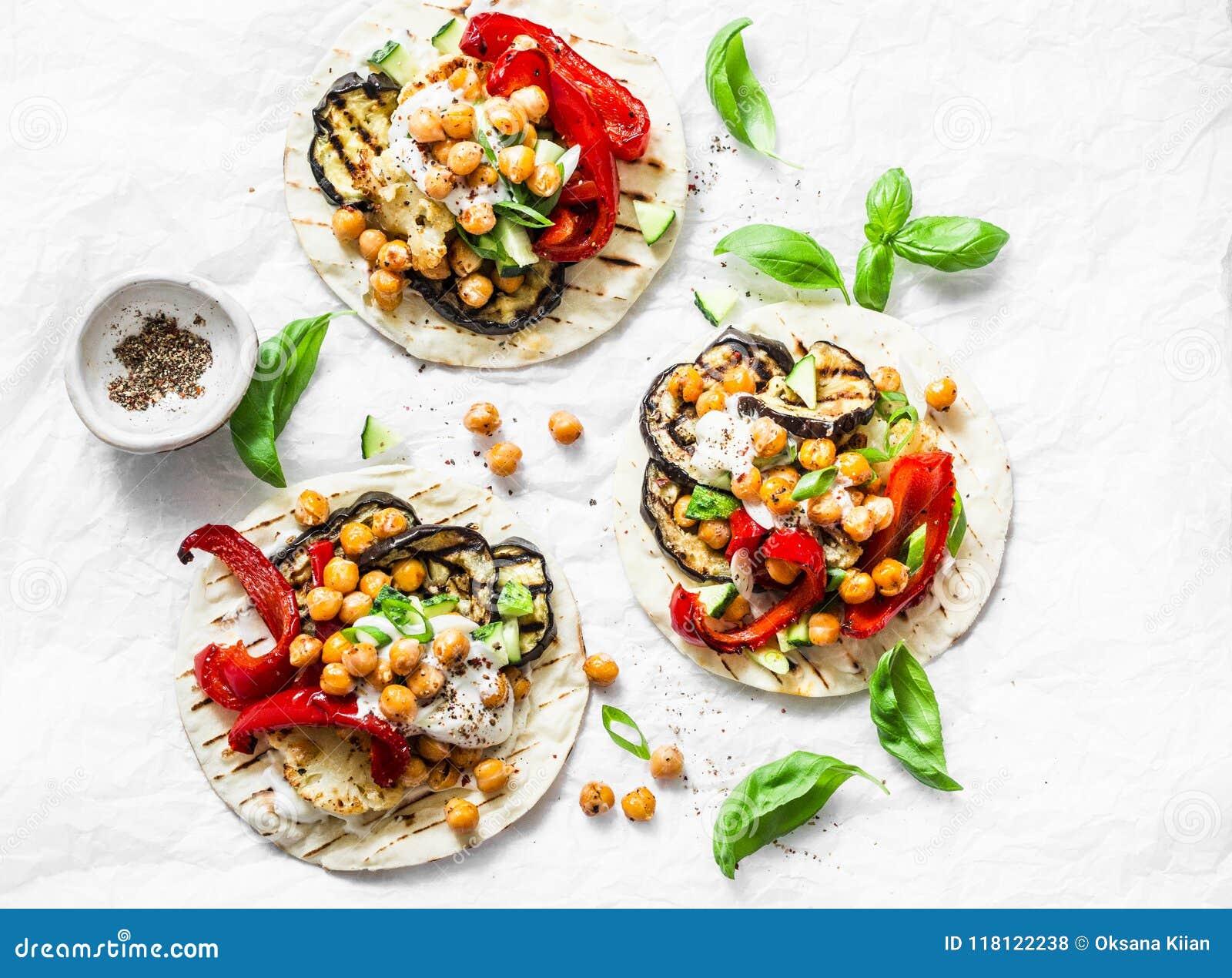 Sommer grillte Gartengemüse und vegetarische Tortillas der würzigen Kichererbsen auf einem hellen Hintergrund, Draufsicht Gesunde