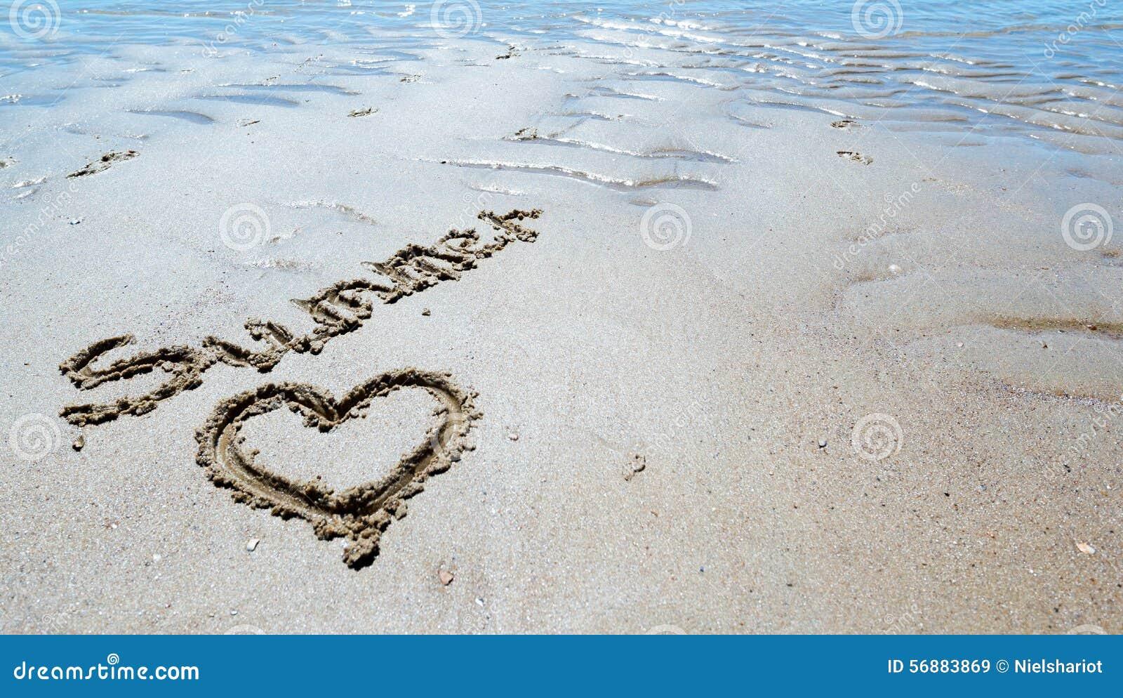 Sommer handgeschrieben im Sand des Strandes mit einem reizenden Herzen