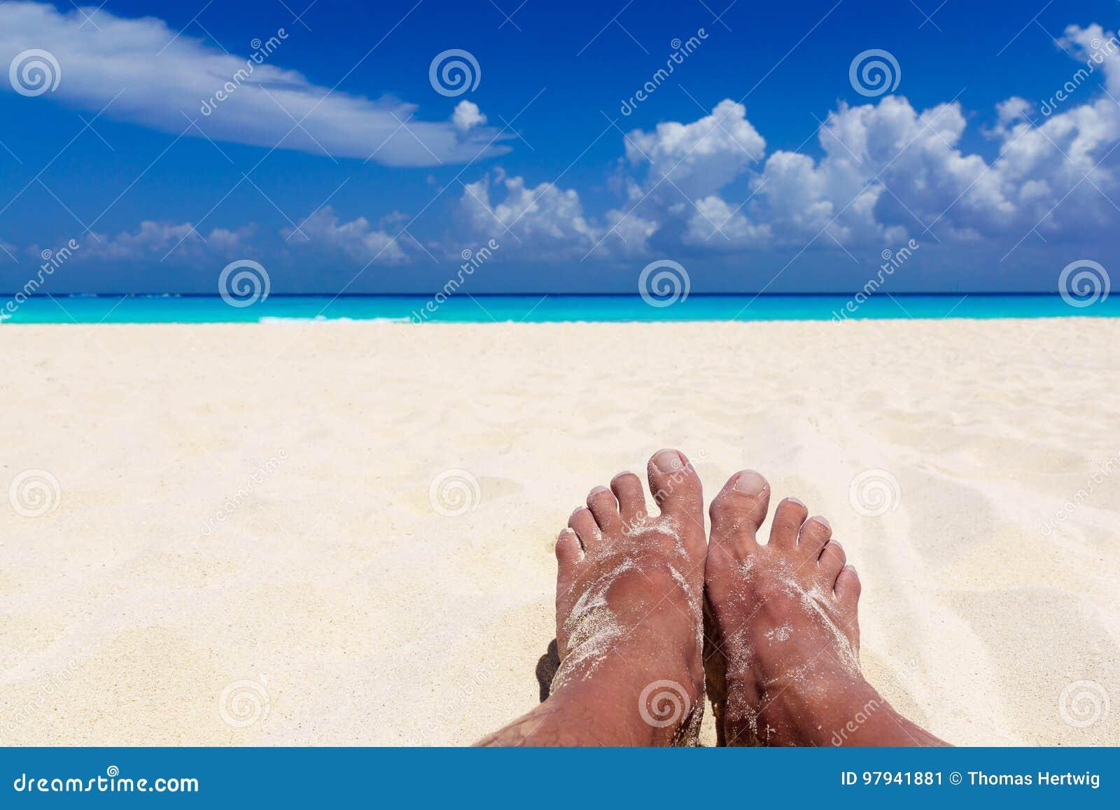 Sommer und Strandkonzept - Füße des Mannes auf tropischem Strand setzen auf den Strand