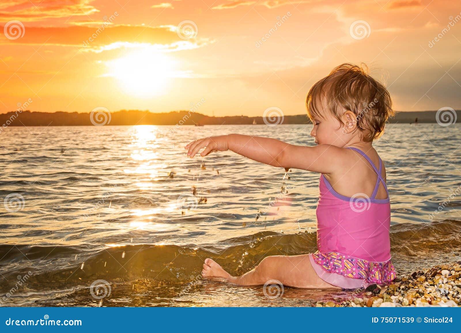 Sommerbaby, das im Meer bei Sonnenuntergang spielt