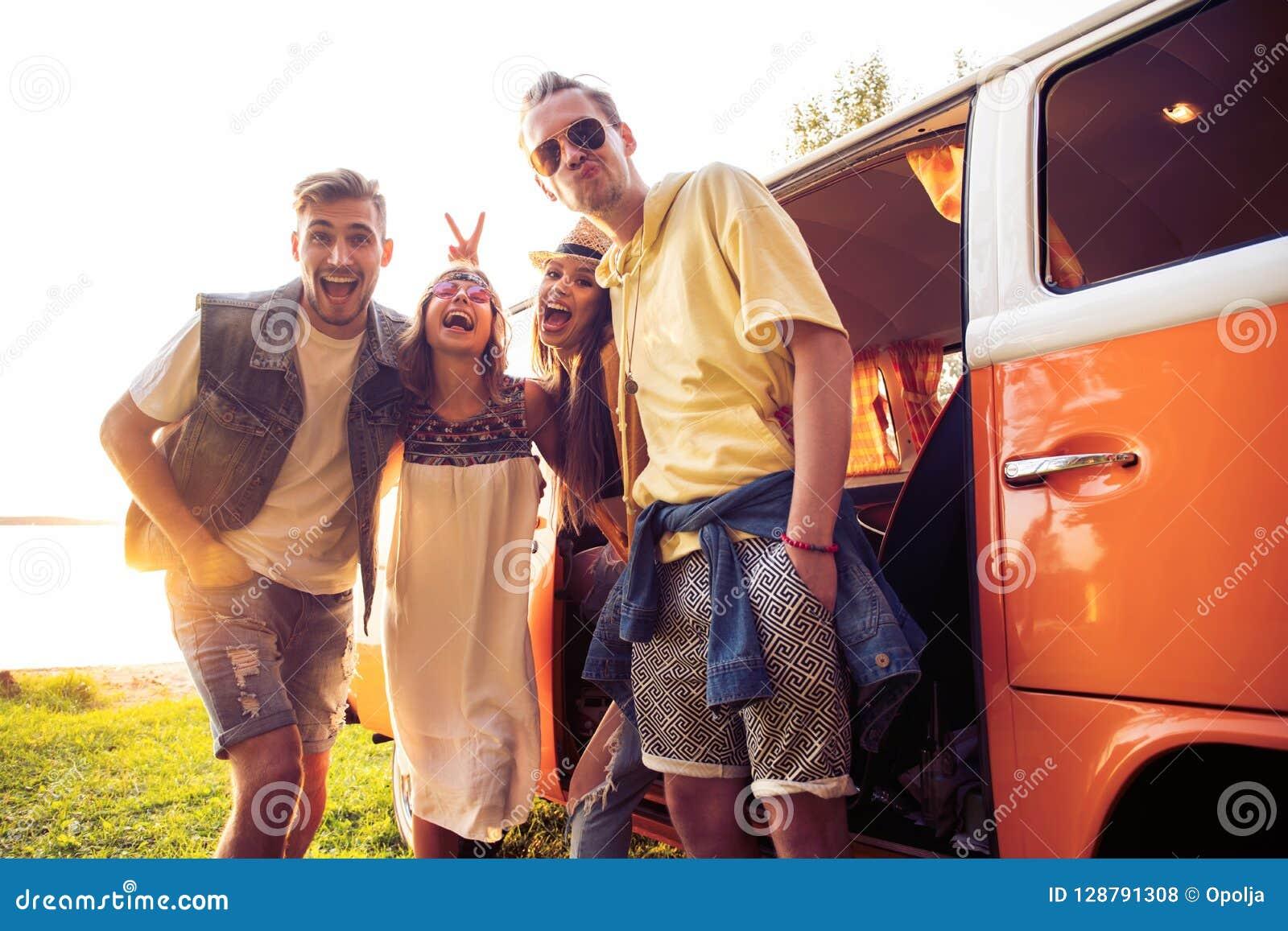 Sommerferien-, Autoreise-, Ferien-, Reise- und Leutekonzept - lächelnde junge Hippiefreunde, die Spaß über Mehrzweckfahrzeug habe