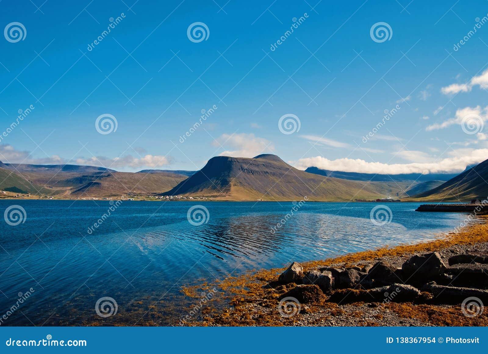 Sommerferien im isafjordur, Island Hügelige Küstenlinie auf sonnigem blauem Himmel Berglandschaft gesehen vom Meer discover