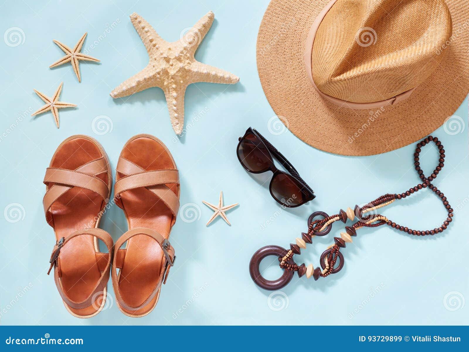 Sommerferienhintergrund, flaches Lagestrandfrauen ` s Zubehör: Strohhut, Armbänder, lederne Sandalen, Sonnenbrillen, Perlen