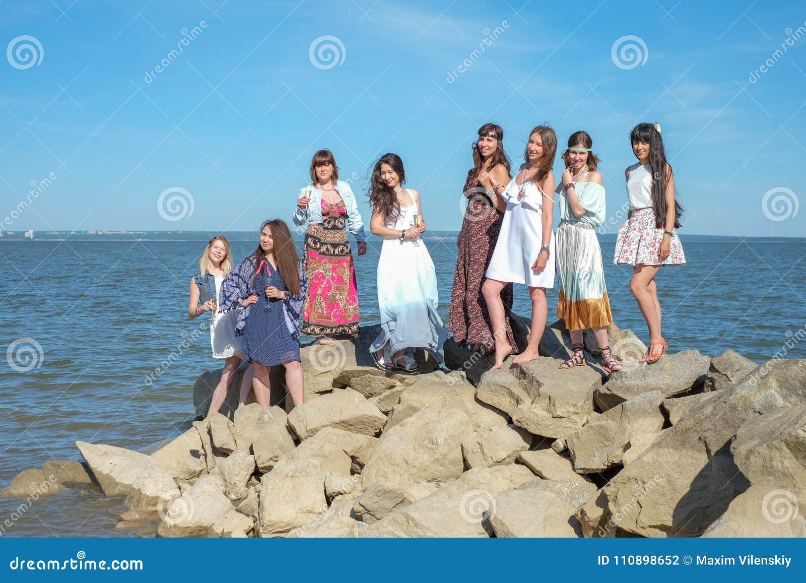 Sommerferienkonzept - Gruppe lächelnde junge Frauen steht auf der Küste still