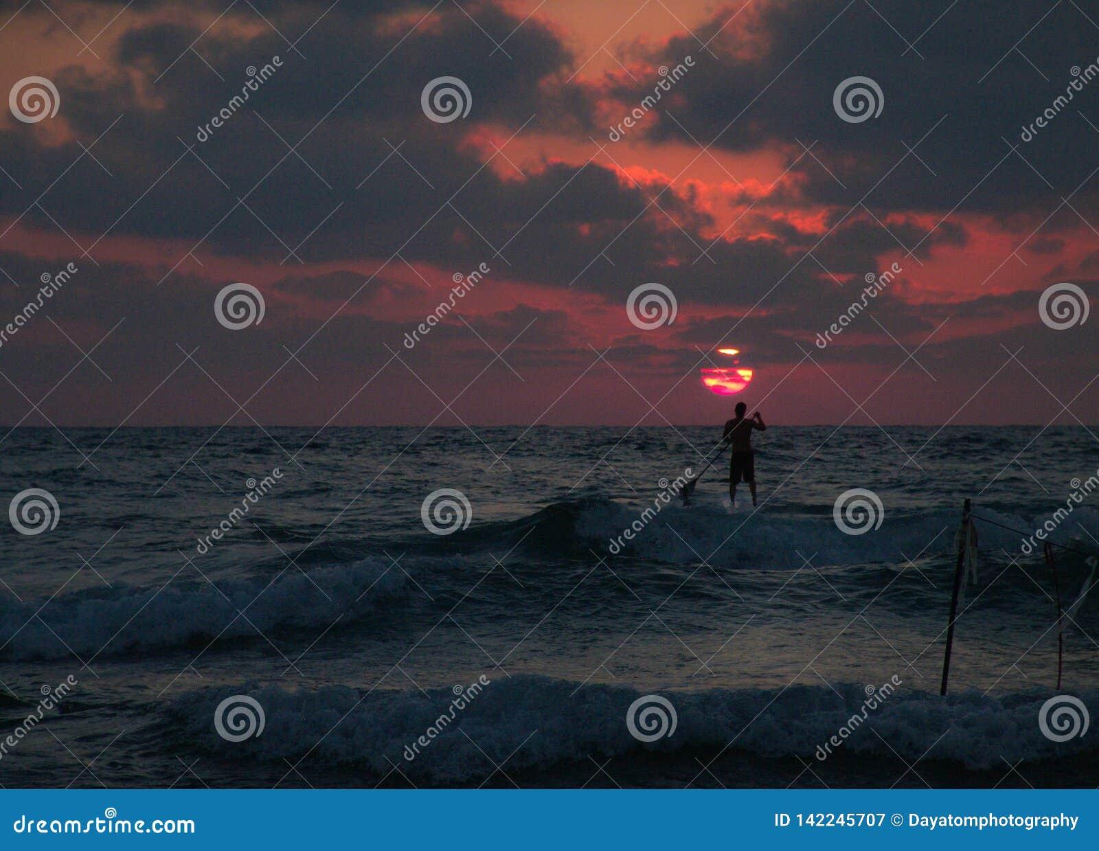 Sommersonnenuntergangansicht eines Strandes unter einem bewölkten Himmel mit einem einzelnen schlürfen Surferschattenbild