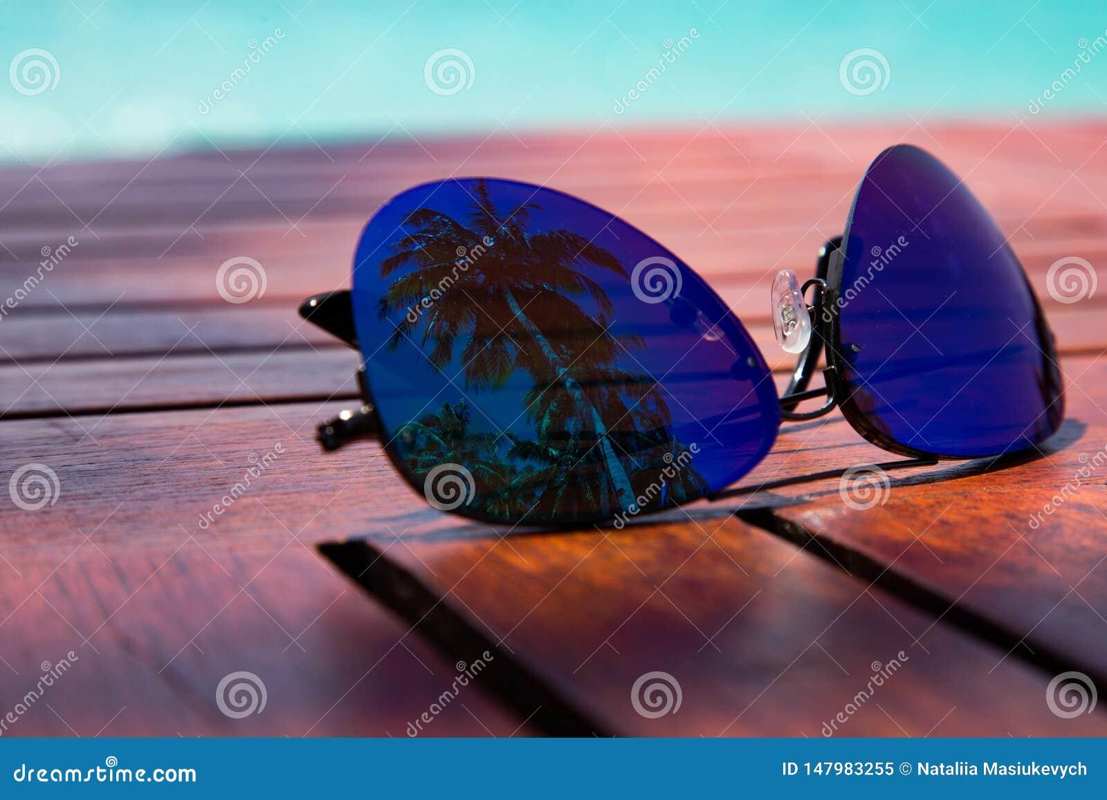 Sommerzeit Artgläser mit Palmenreflexion, die auf einem Holztisch auf der Küste des karibischen Meeres fand