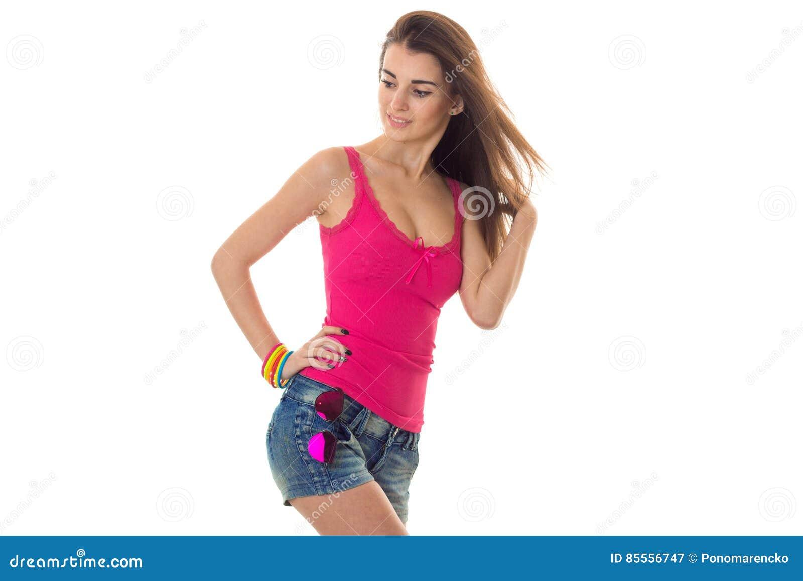 Sommerzeitporträt des jungen hübschen Mädchens in der hellen Kleidung mit der Sonnenbrilleaufstellung lokalisiert auf weißem Hint