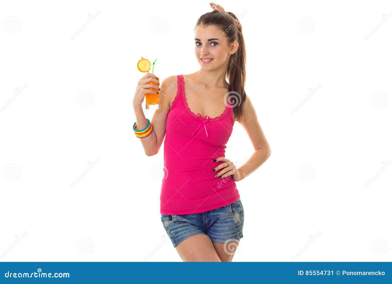 Sommerzeitporträt des jungen reizend Mädchens in der hellen Kleidung mit dem Cocktail bei der Handaufstellung lokalisiert auf wei