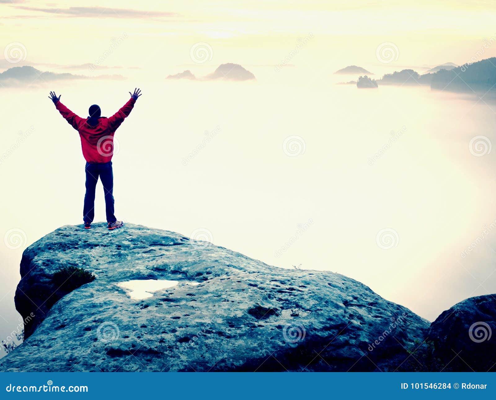Sommità della montagna Armi alzate gesto felice dell uomo Viandante divertente con le mani sollevate nell aria