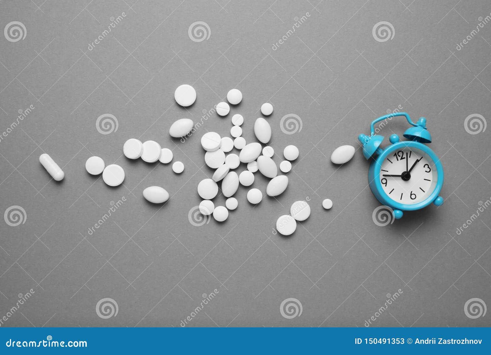 Somníferos y un despertador, concepto del insomnio Problemas de la tensión y del sueño