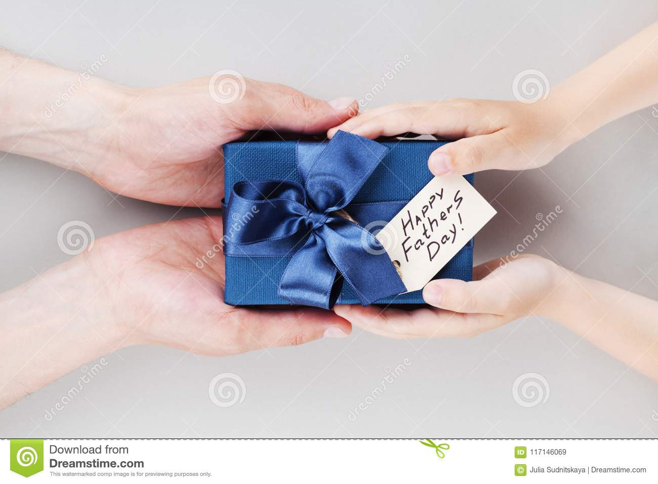 Son gives daddy present or gift box with tag on Happy fathers day. Holiday concept top view.