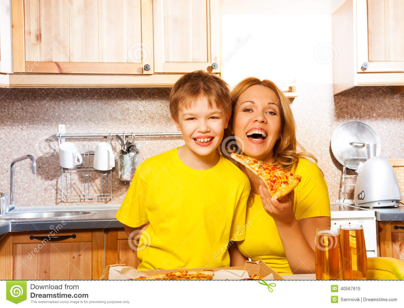 Son and laughing mother holding slice of pizza