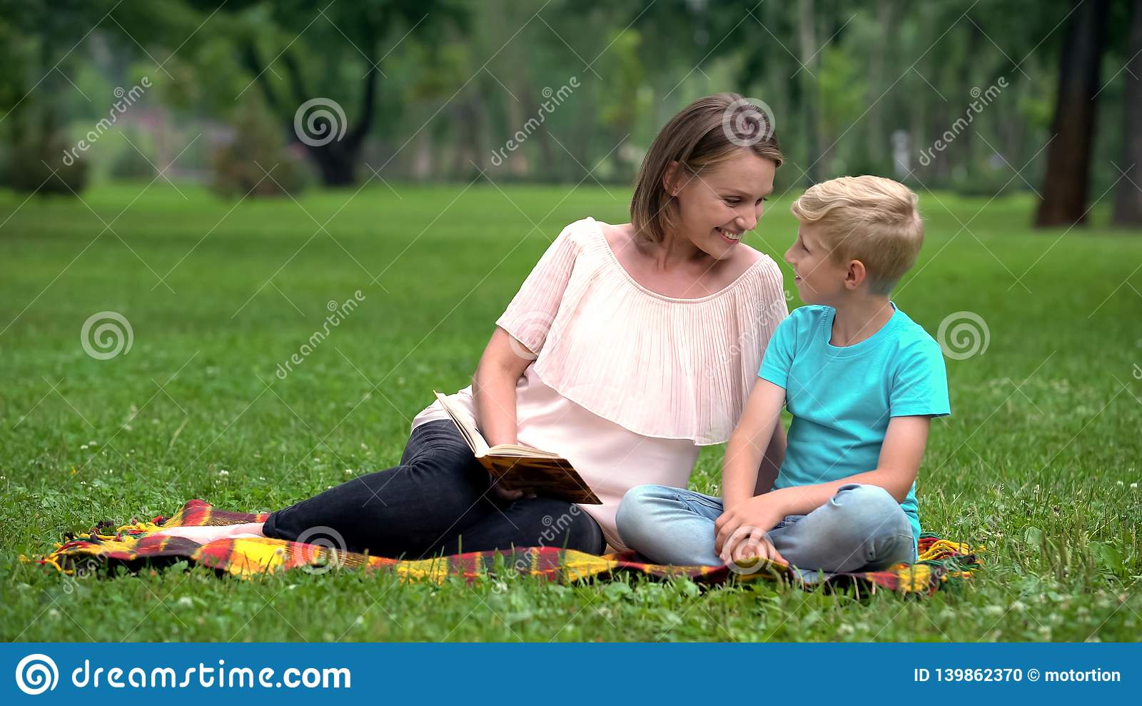 Son and mother reading interesting adventure book, sitting on blanket in park