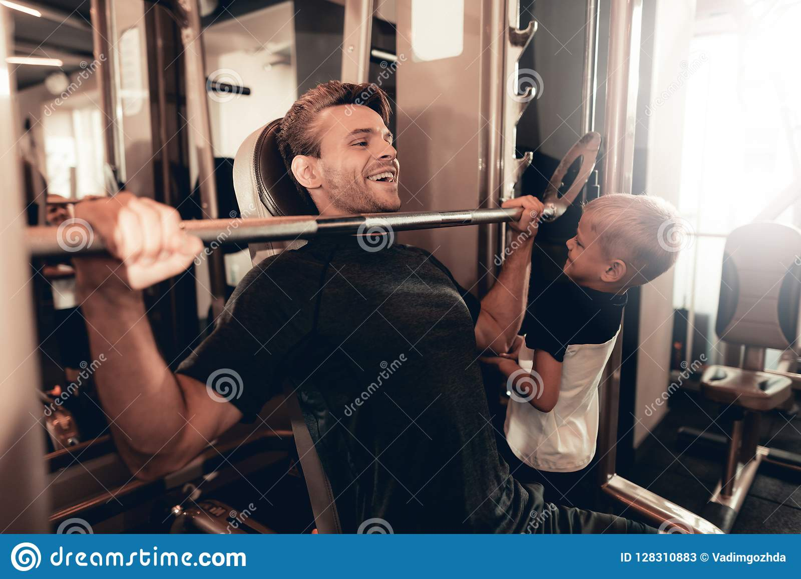 Son Support To Father While Lifting The Barbell.