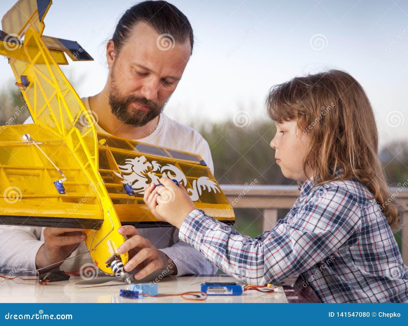Sonen och fadern gjorda hemlagade radio-kontrollerade flygplanet för modellflygplan är handen - gjord inte copyright