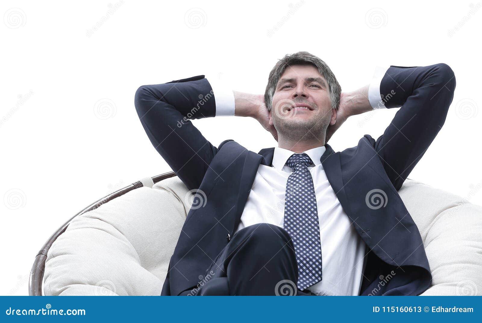 Sonhar o homem de negócios é descansar, sentando-se em uma grande cadeira macia