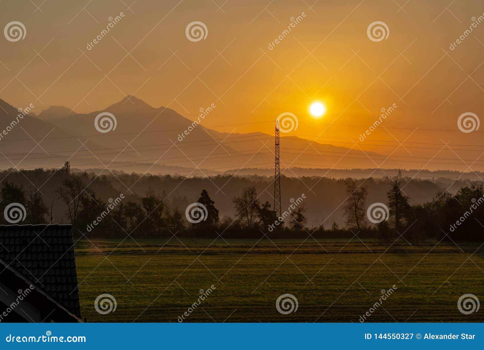 Sonnenaufgang über dem Wald und den Bergen