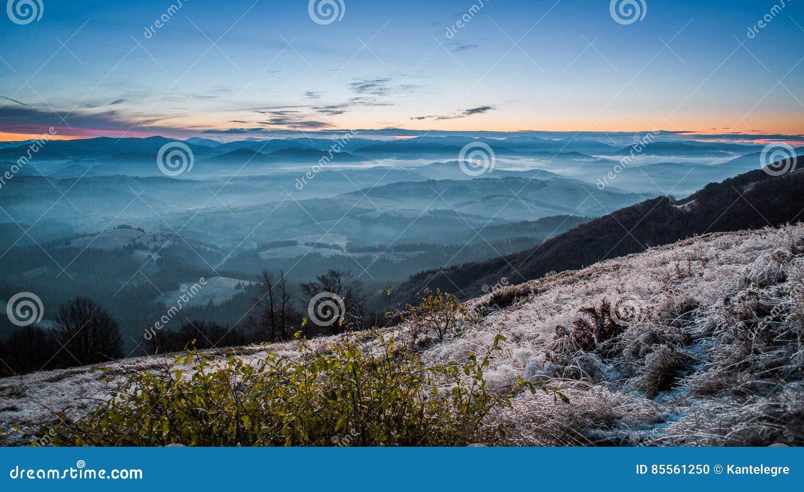 Sonnenaufgang auf Berg mit Nebel und gefrorenem Gras